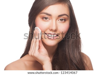 Portrait of young beautiful woman cleaning her face with cotton swab. Isolated on white background - stock photo