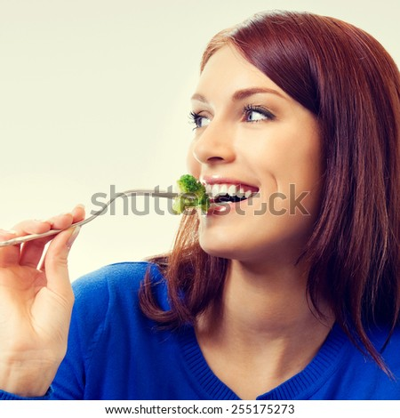Portrait of young beautiful woman eating broccoli - stock photo