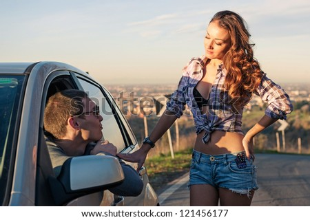 Portrait of young beautiful woman hitchhiker standing at side window and chating with car driver. - stock photo