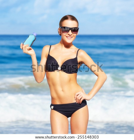 portrait of young beautiful woman in black bikini and sunglasses posing with lotion on blue - stock photo