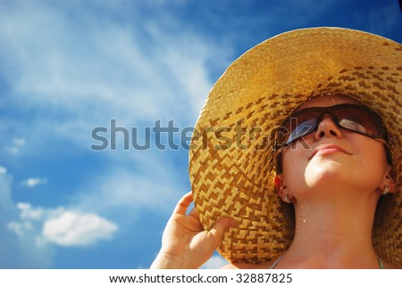 Portrait of young beautiful woman in straw hat and sunglasses - stock photo