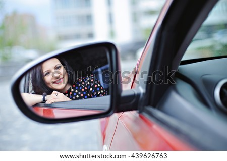 Portrait of young beautiful woman in the reflection of the car mirror. - stock photo
