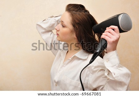 Portrait of young beautiful woman indoor drying her hair - stock photo