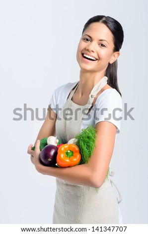 Portrait of young beautiful woman laughing and holding raw vegetables in her arm, peppers, broccoli, dill, mushrooms, aubergine - stock photo