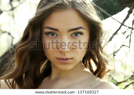 Portrait of young beautiful woman looking at camera on background of spring nature - stock photo