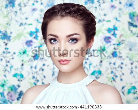 Portrait of young beautiful woman on a background of flowers. Fashion photo. Jewelry and hairstyle. Perfect makeup - stock photo