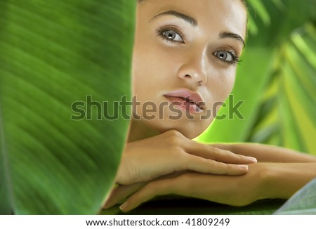 portrait of young beautiful woman on green leafs back - stock photo