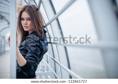 Portrait of young beautiful woman on industrial background - stock photo