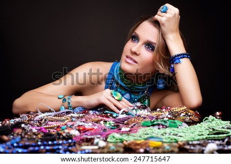 Portrait of young beautiful woman over heap of bijouterie on the table - stock photo