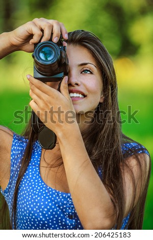 Portrait of young beautiful woman photographed with camera and smiling, on green background summer nature. - stock photo