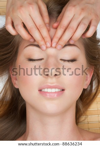 Portrait of young beautiful woman receiving facial massage at spa salon - stock photo