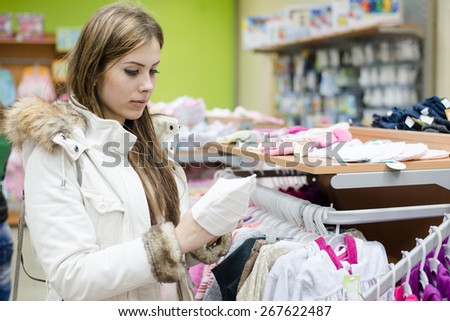 Portrait of young beautiful woman selecting or choosing for buying clothes on interior store background - stock photo
