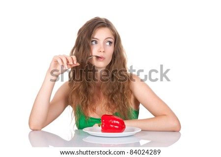 portrait of young beautiful woman sitting at the table, eat red fresh raw pepper on dish, isolated on white background - stock photo