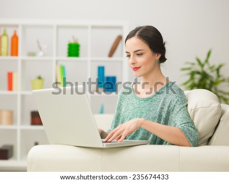 portrait of young beautiful woman sitting on sofa at home using laptop - stock photo