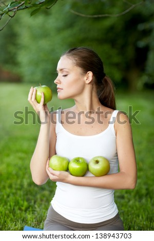 Portrait of young beautiful woman sniffing green apple, outdoors - stock photo
