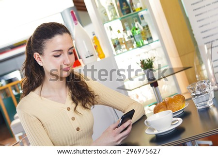 Portrait of young beautiful woman texting a message with her smart phone while having an italian breakfast with cappuccino and brioche in a bar - stock photo