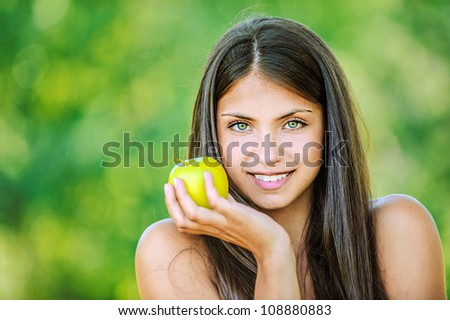 Portrait of young beautiful woman with bare shoulders holding an apple and smiling, on green background summer nature. - stock photo