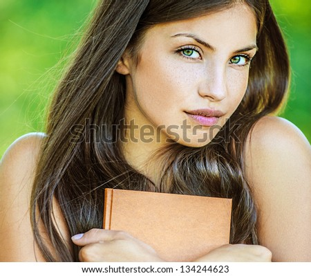 Portrait of young beautiful woman with bare shoulders holding brown book, on green background summer nature. - stock photo