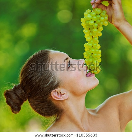Portrait of young beautiful woman with bare shoulders holding grapes, on green background summer nature. - stock photo