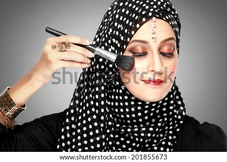 portrait of young beautiful woman with brush for make-up. applying blush on - stock photo