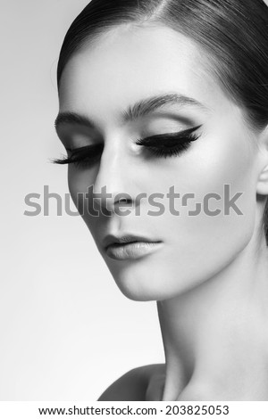Portrait of young beautiful woman with cat eye make-up and false eyelashes, selective focus - stock photo