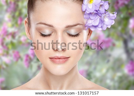 portrait of young beautiful woman with clean skin. On spring background - stock photo