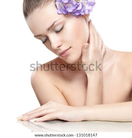 portrait of young beautiful woman with clean skin. with flower in her hair - stock photo