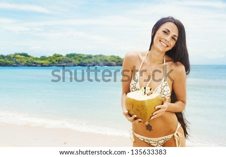 Portrait of young beautiful woman with coconut - stock photo