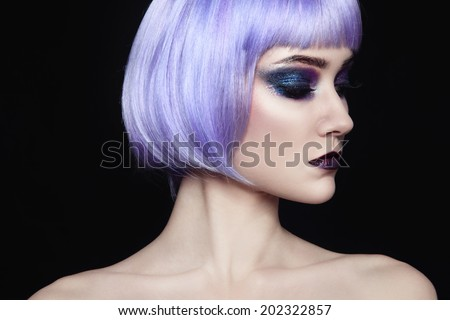Portrait of young beautiful woman with colorful fancy make-up and violet wig - stock photo