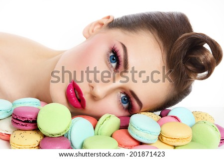 Portrait of young beautiful woman with colorful macaroons over white background - stock photo