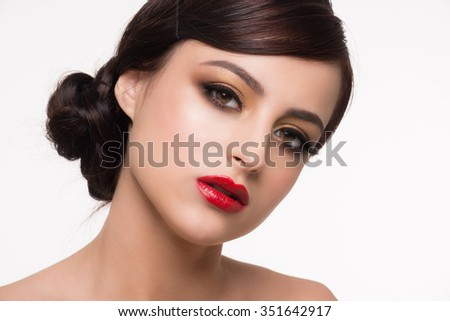 Portrait of young beautiful woman with fashion makeup. Makeup with golden eyeshadow and red lips  - stock photo