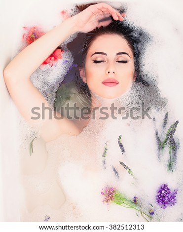 Portrait of young beautiful woman with flowers in the foam bath  - stock photo