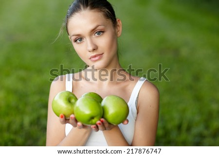 Portrait of young beautiful woman with green apple, outdoors - stock photo