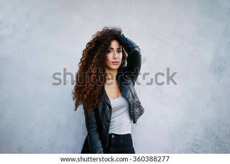 portrait of young beautiful woman with long curly hair wearing posing on a background of gray concrete wall with copy space area for your text .girl showing her gorgeous hair and looking at the camera - stock photo