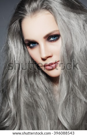 Portrait of young beautiful woman with long grey hair and stylish smoky eyes make-up - stock photo