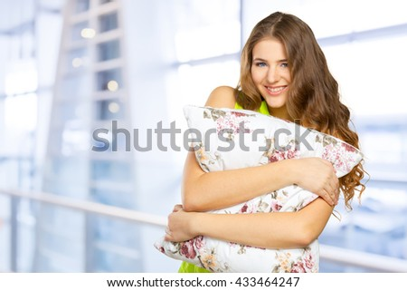 Portrait of young beautiful woman with pillow - stock photo