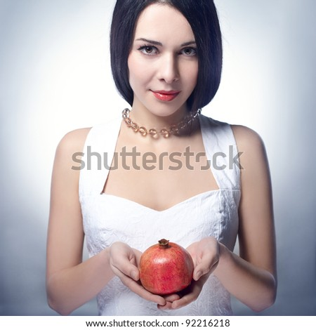 Portrait of young beautiful woman with pomegranates in her hands, on background - stock photo