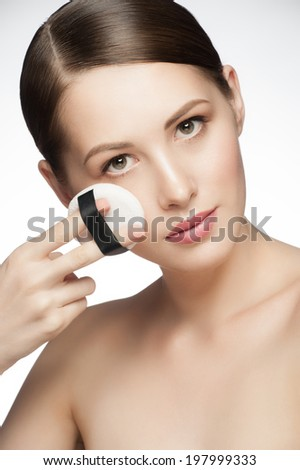 Portrait of young beautiful woman with powder puff. Girl applying makeup. - stock photo