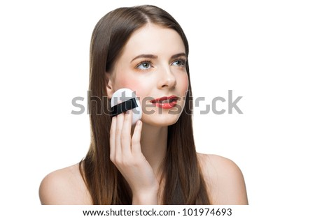 Portrait of young beautiful woman with powder puff. Pretty woman applying make-up. - stock photo
