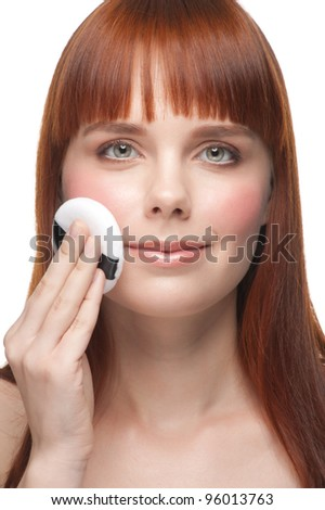 Portrait of young beautiful woman with powder puffs.Pretty woman applying make-up. - stock photo