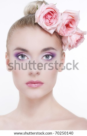 Portrait of young beautiful woman with roses in hair, on white background - stock photo