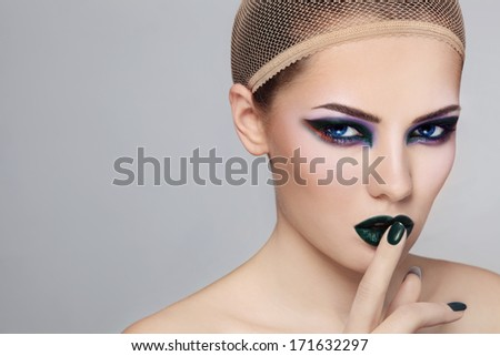 Portrait of young beautiful woman with stylish fancy green make-up and hairnet on her head - stock photo