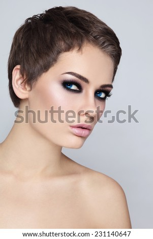 Portrait of young beautiful woman with stylish haircut and smokey eyes - stock photo