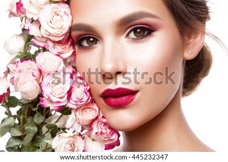 Portrait of young beautiful woman with stylish make-up and colorful roses around her face - stock photo