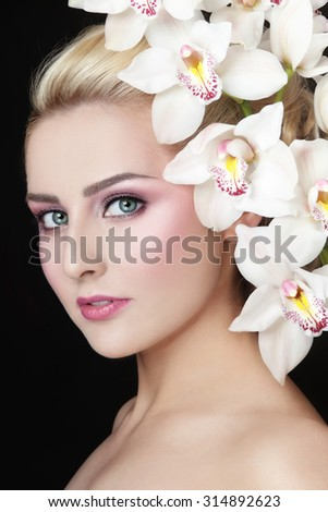 Portrait of young beautiful woman with stylish make-up and white orchid in her hair - stock photo