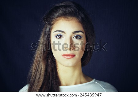 Portrait of young beauty brunette woman against denim background - stock photo