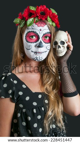 Portrait of young blond girl in black dress with Calavera Mexicana makeup mask and with scull in her hand - stock photo