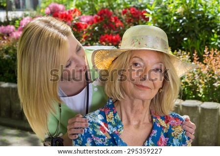 Portrait of Young Blond Nurse Peeking Around Shoulder of Senior Blond Woman Wearing Sun Hat Outdoors in Flower Garden of Retirement Building. - stock photo