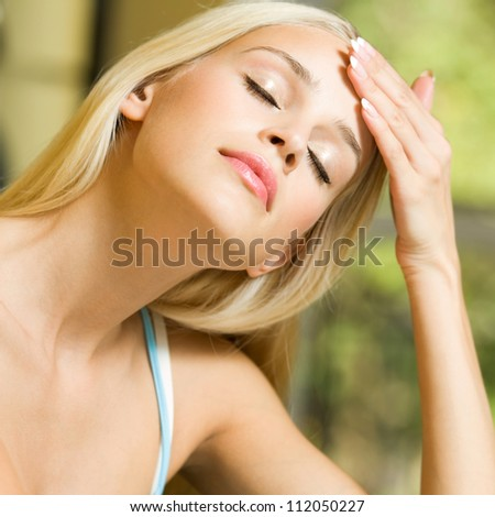 Portrait of young blond woman with headache or applying creme - stock photo