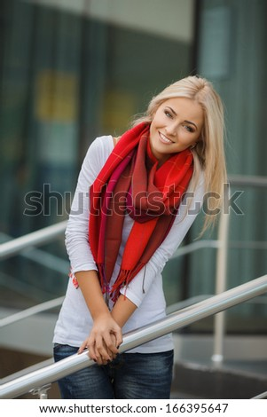 Portrait of young blonde beautiful woman in warm autumn scarf in the street. Ourdoors. - stock photo